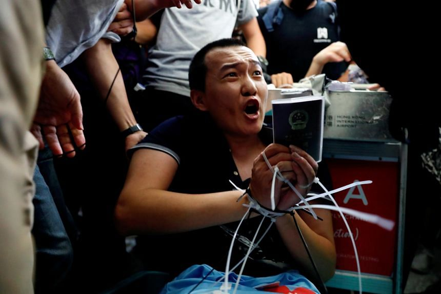 Mr Fu Guohao, the reporter for the Beijing-based newspaper, was tied up with both hands held behind his head on a luggage trolley by a group of masked protesters and then assaulted on Aug 13.