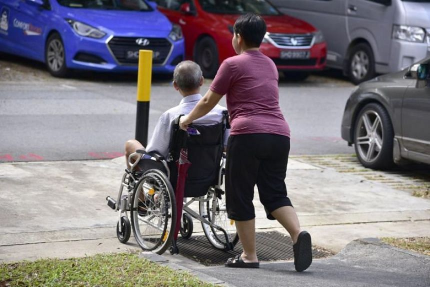 A domestic maid pushing an elderly man on a wheelchair.