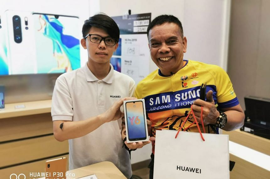 Mechanic Salehim Aman showing the Y6 Pro smartphone he bought with the $100 voucher at Huawei Jurong Point on Aug 13. He feels lucky that he is paying less than the original offer. PHOTO: HUAWEI