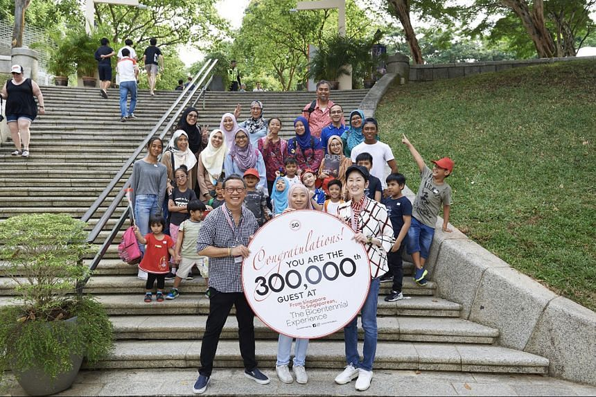 (Front row, from left) Mr Michael Chiang, one of the show's creative directors, the show's 300,000th visitor Qazzira Kamaluddin, and Singapore Bicentennial Office's executive director Gene Tan at Fort Canning.