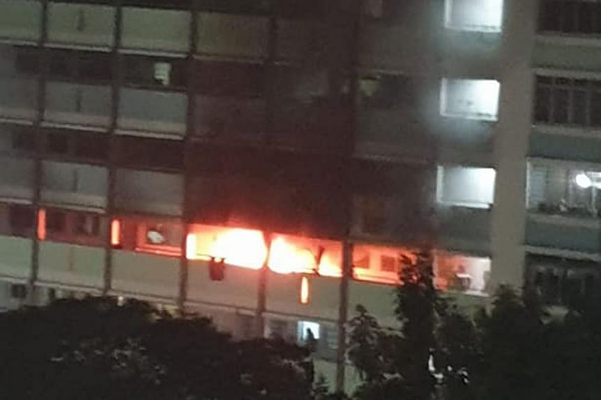 Thick plumes of smoke from a fire at a Jurong West Housing Board flat on Sunday. The SCDF rescued a woman from the flat's kitchen ledge, and she and three others were taken to hospital.