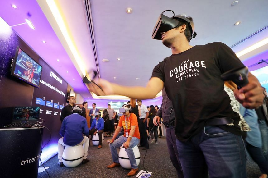 SPH senior software engineer Dinesh Kushwaha trying out a virtual reality space battle game at the Tricentis booth during the SPH Tech Day yesterday.