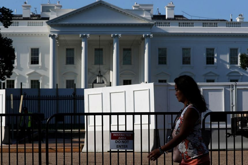 A pedestrian walks past a wall being built at the White House to facilitate work on the new 4m-high fence.
