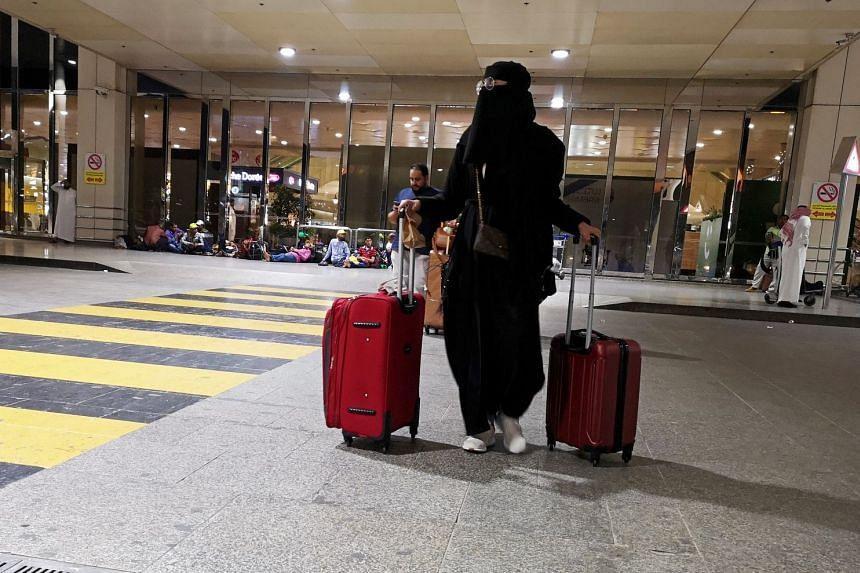 A Saudi woman walks with her luggage as she arrives at King Fahd International Airport in Dammam, Saudi Arabia.