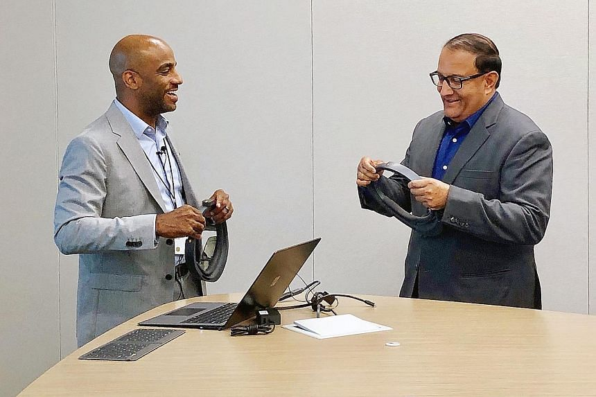 Microsoft principal technical architect Justin Preston giving Mr S. Iswaran a demonstration on the company's HoloLens, which will allow multiple industries to better leverage mixed-reality applications.