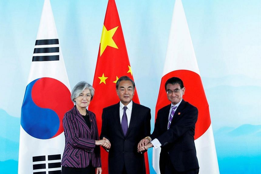 (From left) South Korean Foreign Minister Kang Kyung-wha, Chinese Foreign Minister Wang Yi and Japanese Foreign Minister Taro Kono shake hands ahead of the trilateral foreign ministers' meeting in Beijing on Aug 21, 2019.