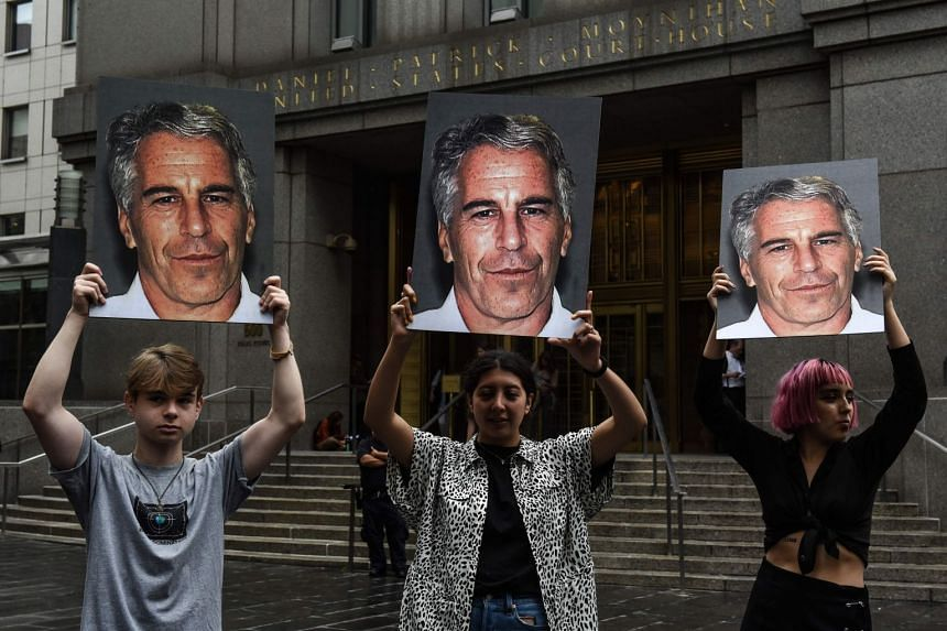 A July 2019 photo shows protesters holding up signs of Jeffrey Epstein in front of the federal courthouse in New York City.