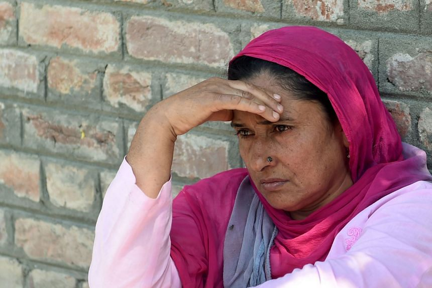 An Indian Kashmiri woman waits outside a police station after her relative was detained during night raids in Srinagar.