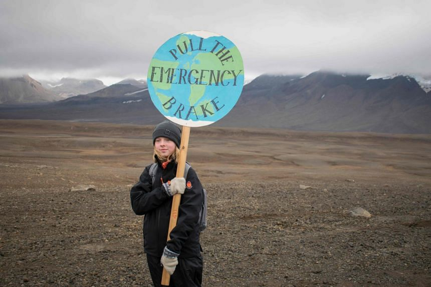 """In a photo taken on Aug 18, 2019, an Icelandic girl holds a """"Pull the emergency brake"""" sign near where a monument was unveiled at the site of Okjokull, Iceland's first glacier lost to climate change."""