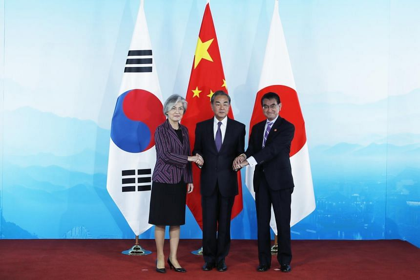 The foreign ministers of (from left) South Korea Ms Kang Kyung-wha, China Mr Wang Yi and Japan Mr Taro Kono shake hands ahead of their trilateral meeting at Gubei Town in Beijing on Aug 21, 2019.