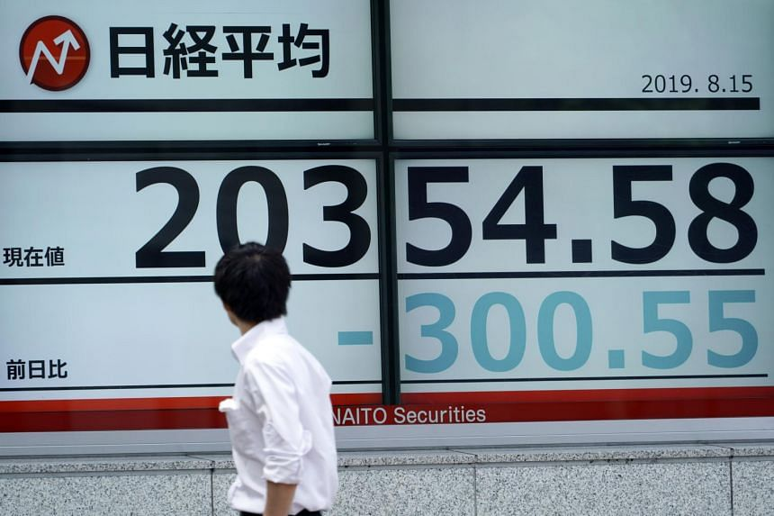 A man looks at an electronic stock board showing Japan's Nikkei index at a securities firm in Tokyo on Aug 15, 2019.