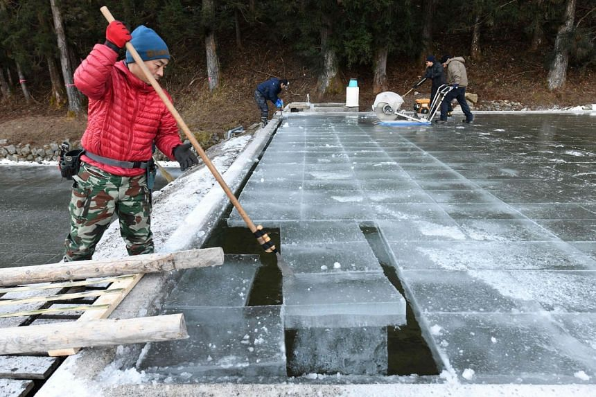 A worker removing a block of natural ice after it was cut from an open-air pool at a factory in Nikko, Japan.