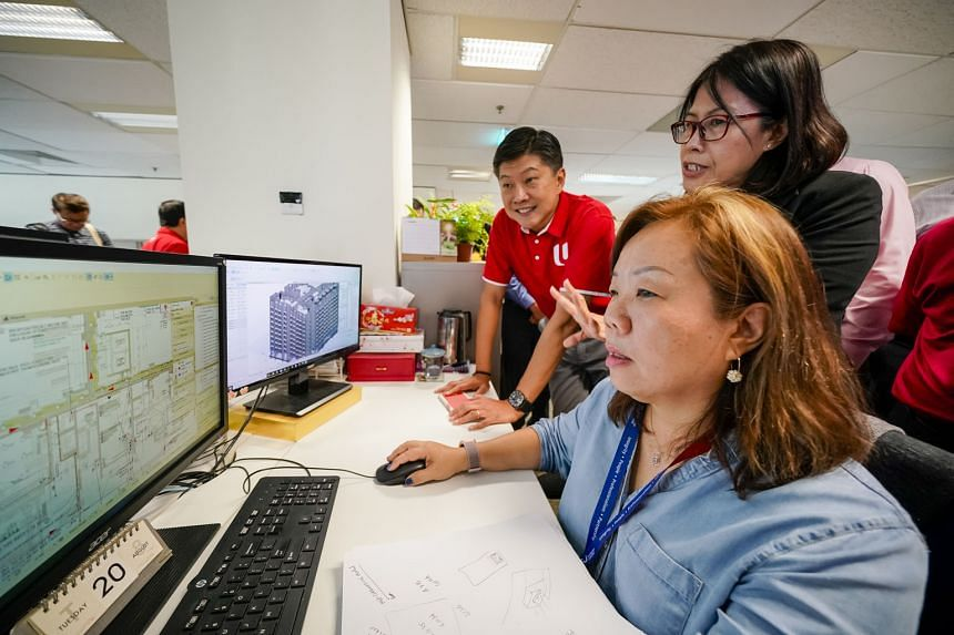 Surbana Jurong mechanical and electrical designer Jerine Tay (seated) and technical manager Tan Siew Fong showing NTUC secretary-general Ng Chee Meng how their team coordinates a design with different colour coding in the drawing using digital software. M