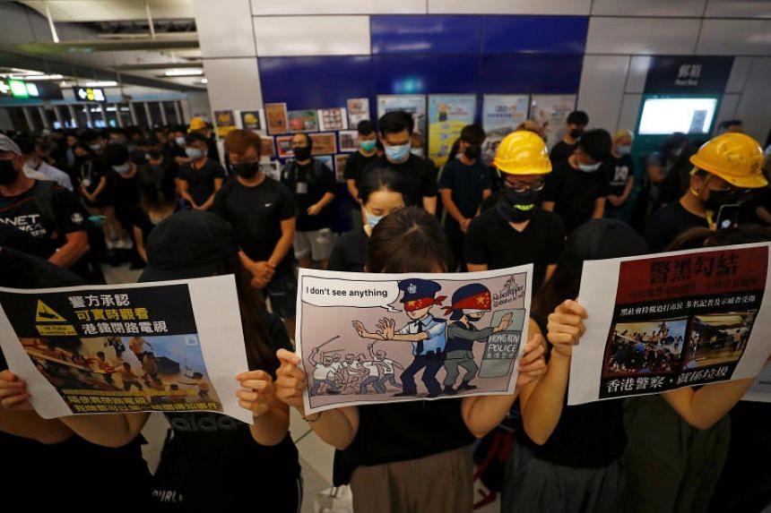 People hold up slogans during a silent sit-in gathering at Yuen Long MTR station in Hong Kong on Aug 21, 2019.