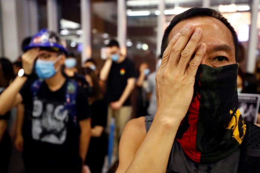 People protest during a silent sit-in gathering at Yuen Long MTR station in Hong Kong on Aug 21, 2019.