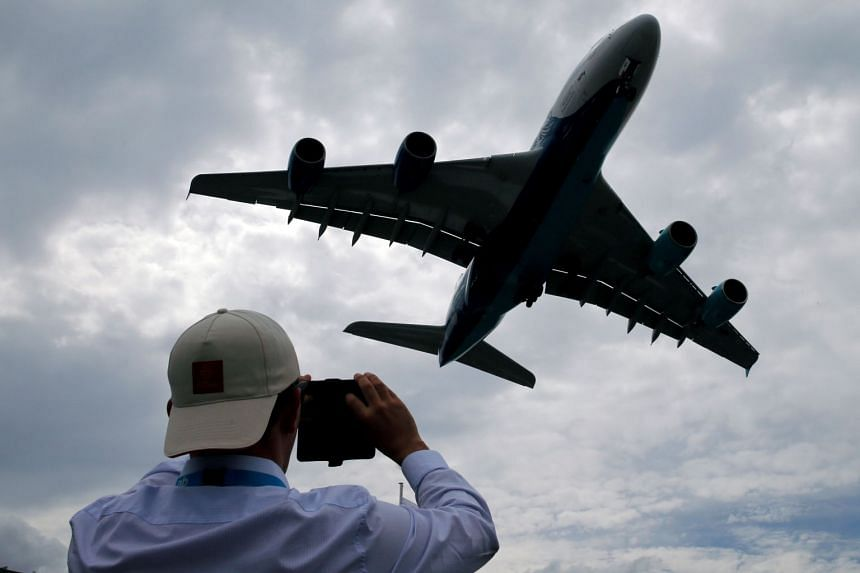 A visitor takes a picture of an Airbus A380 as it lands after an air display at the 53rd International Paris Air Show..