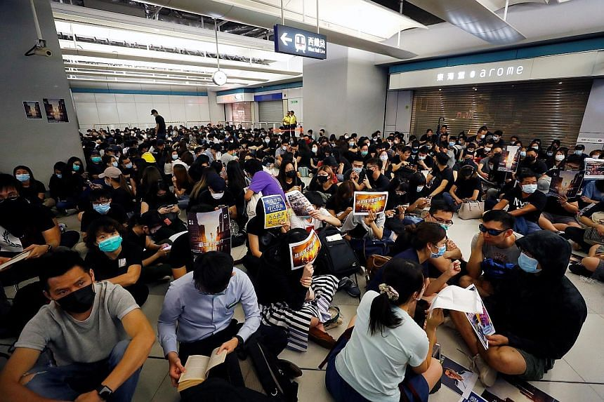 Left: A silent sit-in protest yesterday at Hong Kong's Yuen Long MTR station, which was the scene of an attack on protesters by suspected triad gang members a month ago. The attack left nearly 50 people in hospital, including passers-by. PHOTOS: REUT