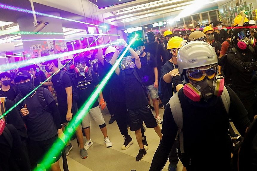 Protesters facing off with riot police inside the Yuen Long station yesterday. Some put on hard hats and gas masks, while others sprayed fire extinguishers and poured detergent, beer and oil on the concourse to impede entry by the police.