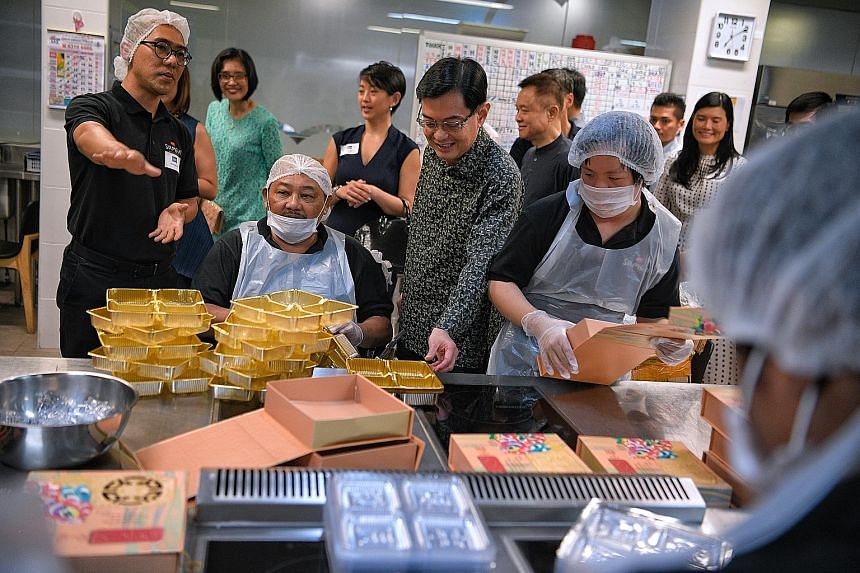 Deputy Prime Minister Heng Swee Keat speaking to Samsui Kitchen staff and volunteers at the Enabling Village in Lengkok Bahru yesterday. They were preparing mooncake boxes before the National Volunteer and Philanthropy Centre Company of Good Fellowsh