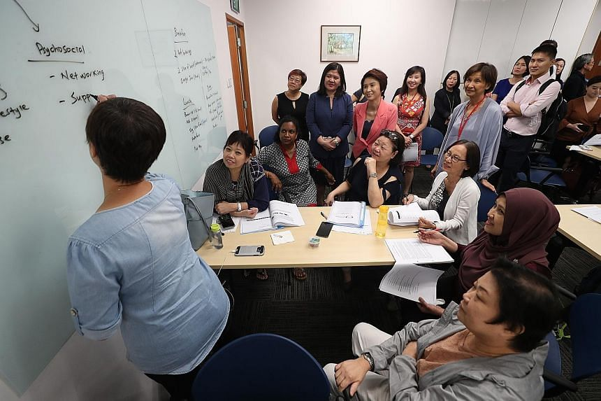 Senior Parliamentary Secretary for Manpower and Education Low Yen Ling (in pink blazer) observing a LifeWork course for mature workers with Centre for Seniors executive director Lim Sia Hoe (in pale grey, standing).
