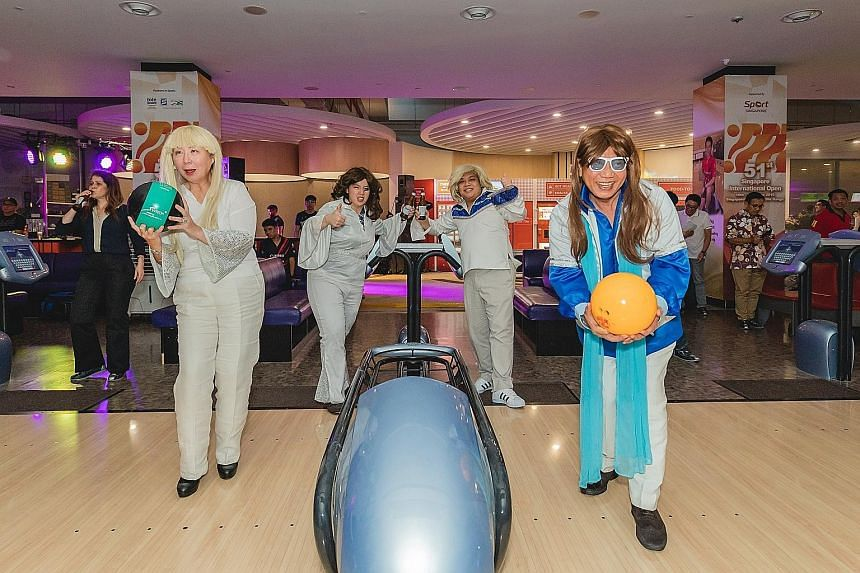 """The Singapore Bowling Federation (SBF) celebrating its """"Let's Rock and Bowl"""" Canon Ambassador Night that also served to commemorate the long-standing SBF-Canon partnership. SBF president Jessie Phua (left) and her husband Jimmy joined the fun bowl la"""