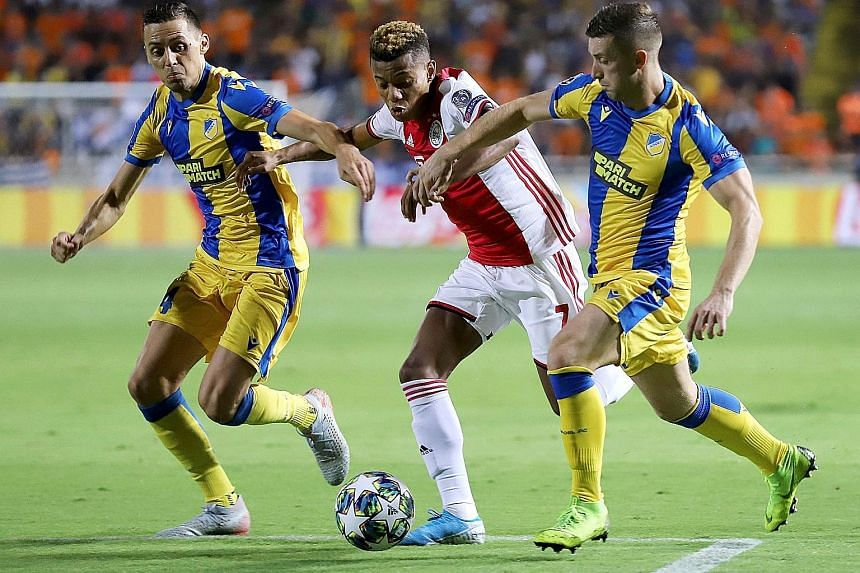 Ajax forward David Neres (centre) is challenged by Apoel Nicosia players during the Uefa Champions League play-off match at the GSP stadium in Nicosia on Tuesday. PHOTO: AGENCE FRANCE-PRESSE