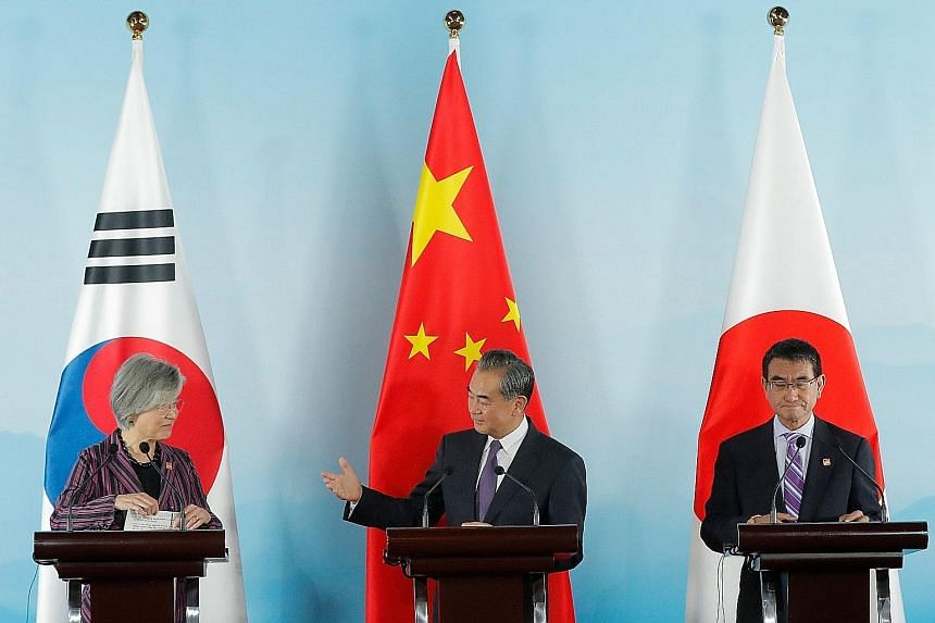 Chinese Foreign Minister Wang Yi (centre) with South Korean Foreign Minister Kang Kyung-wha (left) and Japanese Foreign Minister Taro Kono at a press conference after their meeting in Beijing yesterday. China, Japan and South Korea agreed to continue