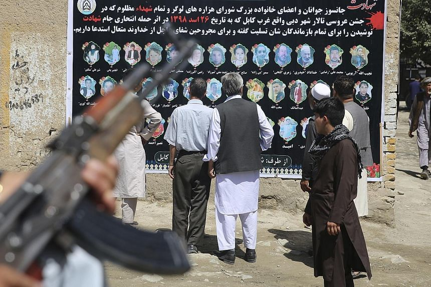 """A banner with pictures of victims of last Saturday's wedding party bombing in Kabul, which was claimed by ISIS. Afghan officials say ISIS has been reduced to staging suicide attacks against """"soft"""" targets, but border province leaders say ISIS forces"""