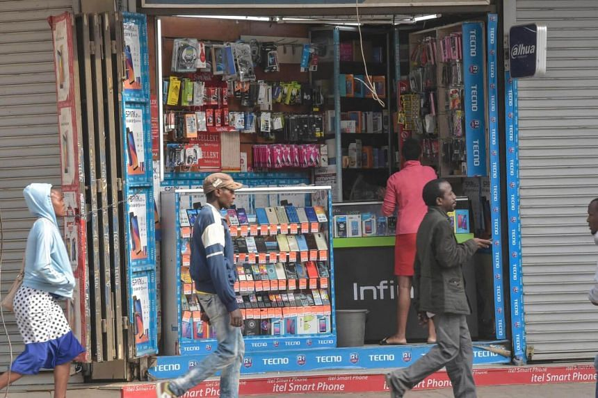 In a photo taken on July 24, 2019, pedestrians walk past a mobile shop in downtown Nairobi. Sub-Saharan Africa has proven fertile for mobile microlending, with the region home to 395.7 million mobile-money accounts in 2018.