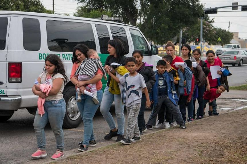 In this photo taken on June 12, 2019, Central American migrant families arrive at a Catholic Charities respite center after being released from federal detention in McAllen, Texas.