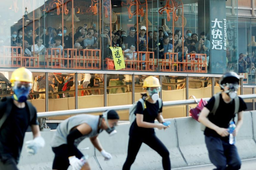 People inside a restaurant watch as protesters attend a demonstration in support of the city-wide strike and to call for democratic reforms outside Central Government Complex in Hong Kong on Aug 5, 2019.