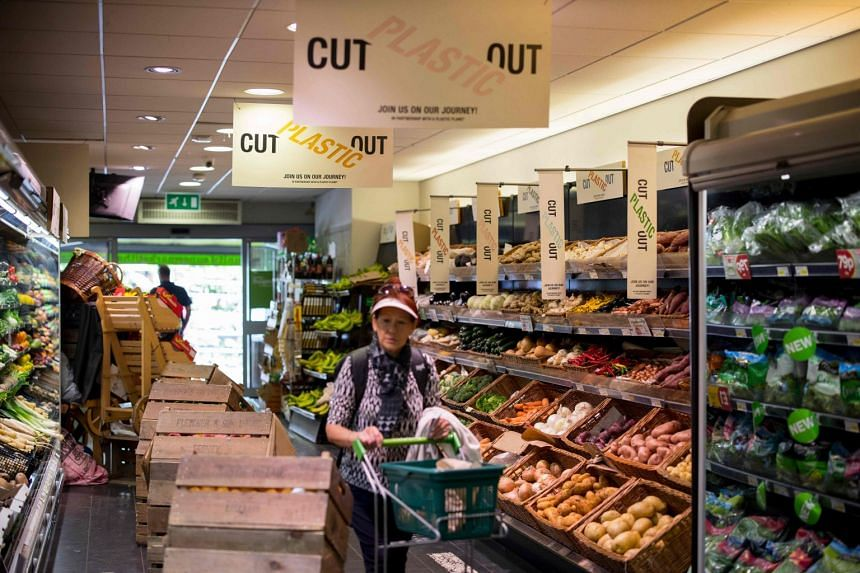 Signs promoting plastic-free packaging are seen as shoppers browse the shelves at Budgens supermarket in Belsize Park, north London. Big brand shops in Britain, bowing to increasing pressure from environmentally conscious consumers, have begun taking