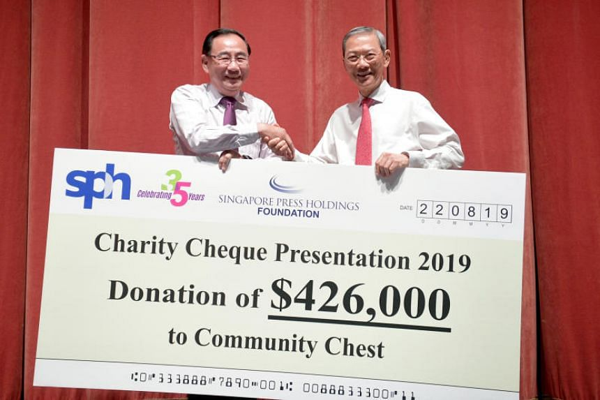 Community Chest chairman Phillip Tan (left) receiving a cheque of $426,000 from SPH chairman Lee Boon Yang on Aug 22, 2019.