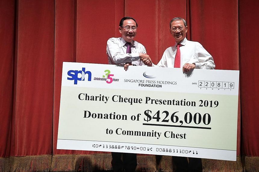 Dr Lee Boon Yang (right), Singapore Press Holdings and SPH Foundation chairman, presenting a cheque to Community Chest chairman Phillip Tan. The money will go to the Special Education Financial Assistance scheme and 20 charities. The anniversary conc