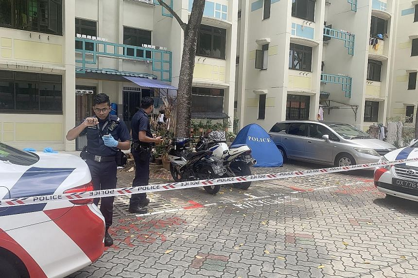 The police at the foot of Block 26 Toa Payoh East where an 84-year-old man's body was found. He is believed to have fallen from the 10th storey, where he lived in a unit with his wife. She reportedly died in hospital after suffering a heart attack on