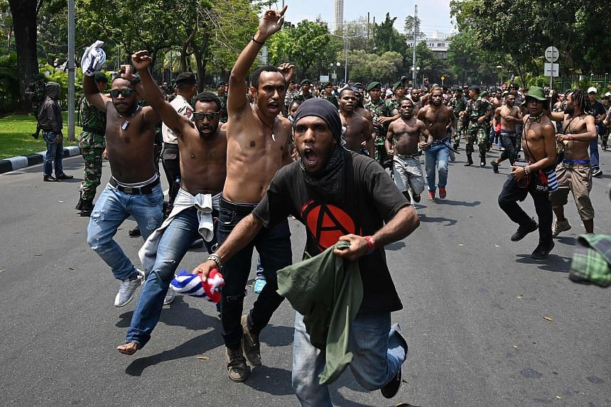 Papuan students breaking away from a line of police and military personnel during a rally, demanding the right to self-determination and an end to racism and colonialism in West Papua, in front of the army's headquarters in Jakarta yesterday. Riots a