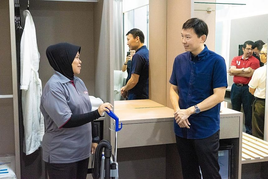 Senior Minister of State for Trade and Industry Chee Hong Tat speaking with a WIS Holdings staff member, who will be trained in housekeeping, at a mock hotel room set up in the company's training academy for environmental services workers.