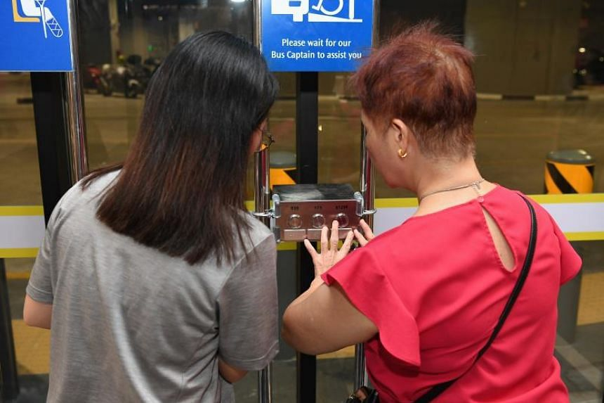 SMRT staff guiding a visually handicapped person at the Yishun Integrated Transport Hub on Aug 23, 2019.