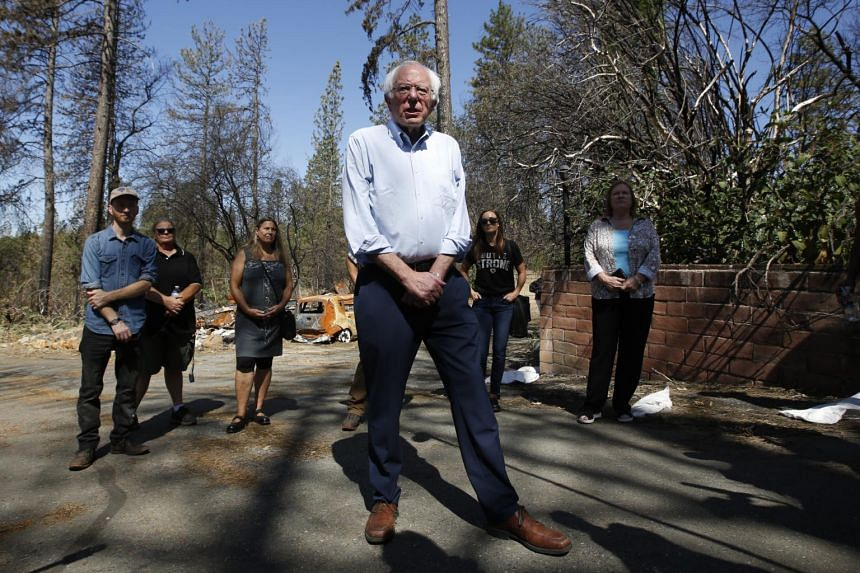 Independent Senator Bernie Sanders tours a mobile home park that was destroyed by last year's wildfire in Paradise, California. Severe floods and wildfires over the last year have raised concerns about immediate effects of changing temperatures.