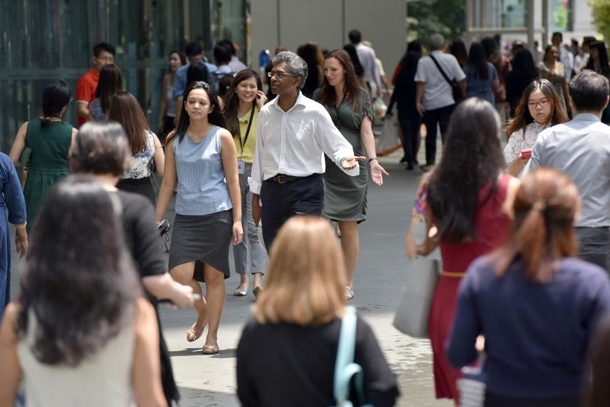 Office workers walking outside Raffles Place MRT Station, on May 7, 2019.