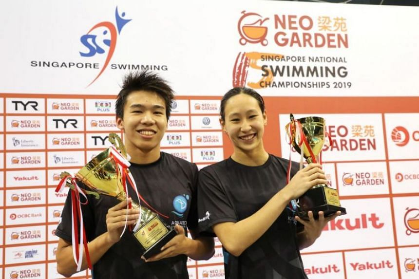 In a photo from June 22, 2019, Jonathan Tan and Cherlyn Yeoh raise their trophies at the Neo Garden 15th Singapore National Swimming Championships at the OCBC Aquatic Centre in Singapore.