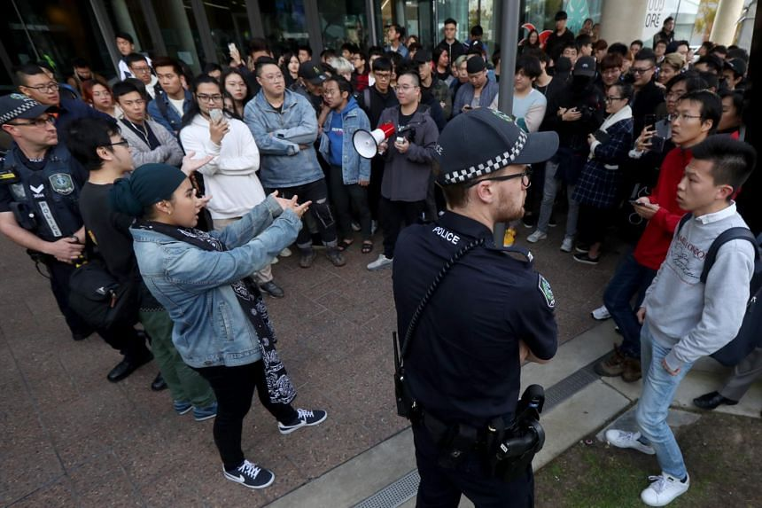 Australian policemen separate pro-China and pro-Hong Kong students during a protest outside a university in Adelaide, on Aug 16, 2019.