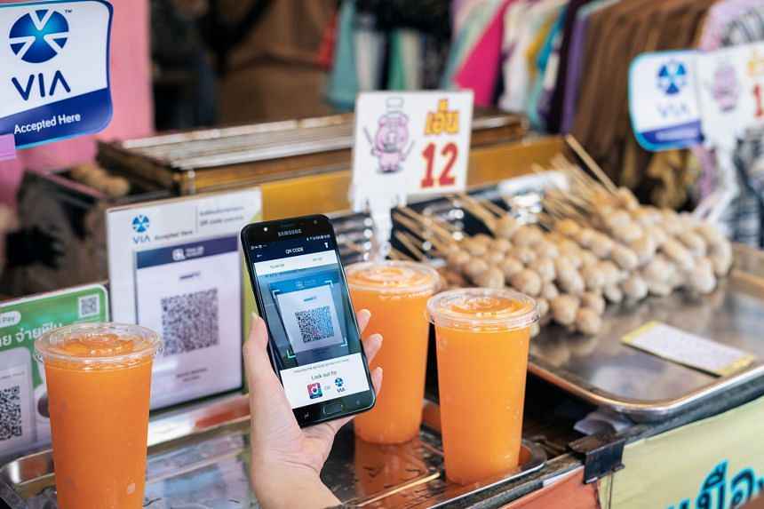 A Singtel Dash user making payment at Bangkok's Chatuchak weekend market. Singtel Dash can be used in Thailand and Japan as part of VIA, a cross-border payment alliance.