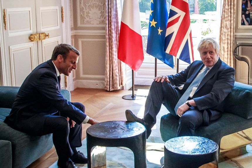 Boris Johnson places his foot on the table during a meeting with French President Emmanuel Macron.