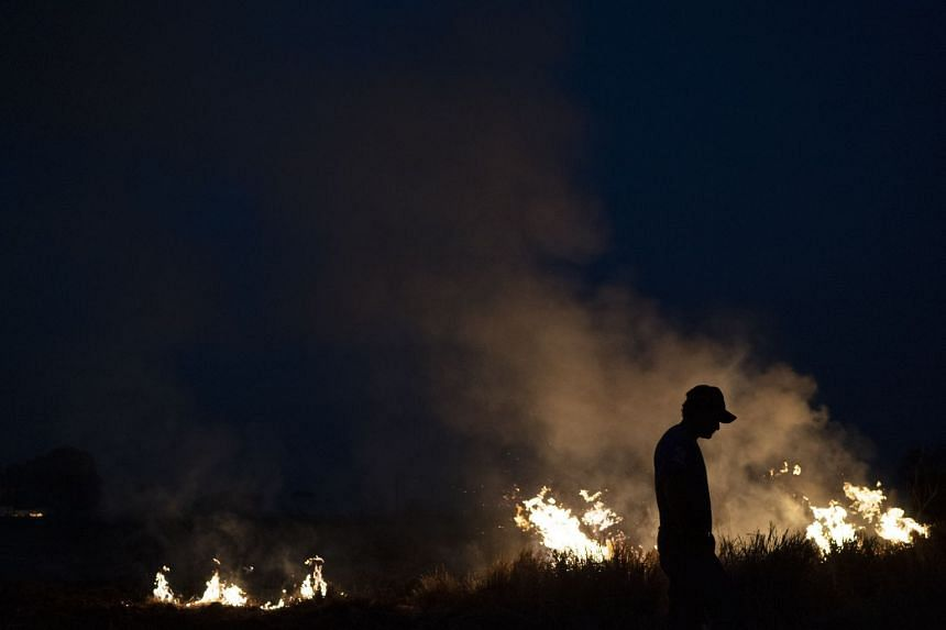 Neri dos Santos Silva is silhouetted against an encroaching fire threat after he spent hours digging trenches to keep the flames from spreading to the farm he works on.