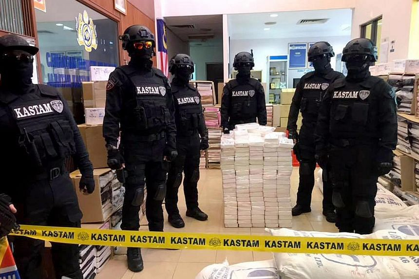 Malaysian Customs officials with the record 467kg of ketamine and about 3,200kg of cocaine they found in raids on Sunday, in what is the biggest drug seizure in the country's history. PHOTO: JABATAN KASTAM DIRAJA MALAYSIA/ FACEBOOK