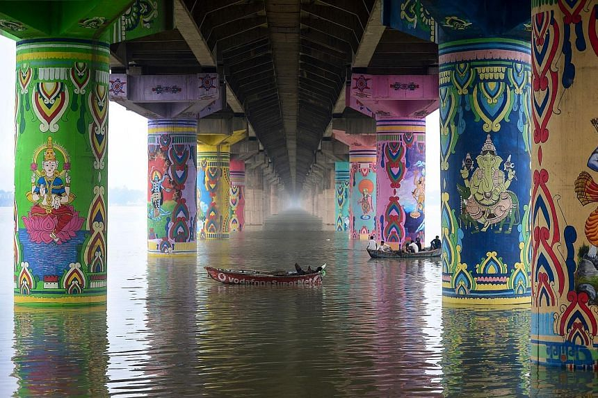 """Boats sailing on the Ganges river under the Shastri bridge in the city of Prayagraj, in India's northern state of Uttar Pradesh, on Thursday. The bridge's pillars were given a new look as part of the """"Paint My City"""" project last December for the Kumb"""