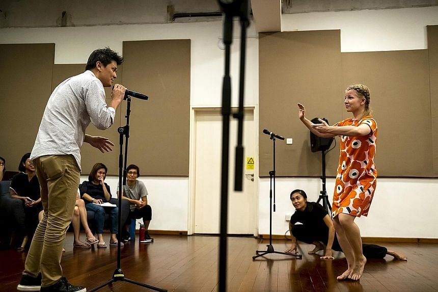 Ang Xiao Ting (in black, on floor) and Sini Rautjoki (in orange) react to an audience member speaking into the microphone in Ming Poon's The Pledge at Project Utopia.