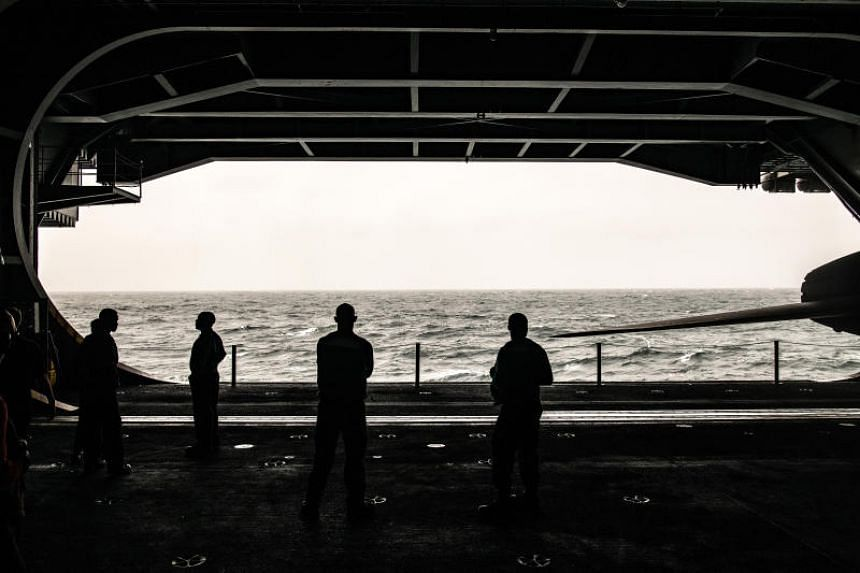 A photo taken on Aug 10 shows sailors aboard the USS Abraham Lincoln, an aircraft carrier, in the North Arabian Sea.