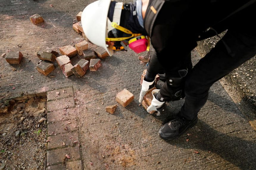 A demonstrator breaks bricks to throw them to riot police as they clash during a protest in Hong Kong on Aug 24.